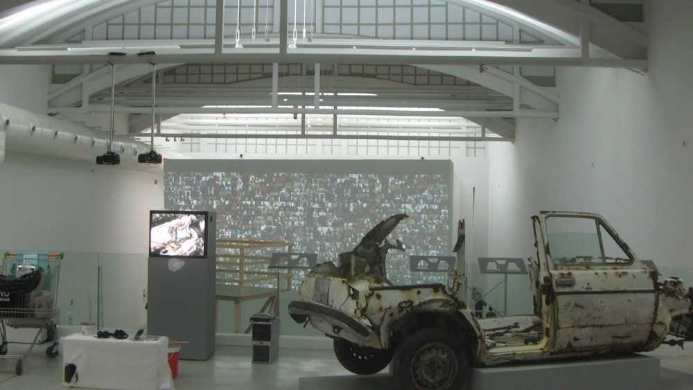 """Barbara Fluxa's """"Car project, excavating XX century´s end,"""" at the entrance to the exhibition, overlooking the lower floor, Chris Baker's """"Hello World! ! or: How I Learned to Stop Listening and Love the Noise"""""""
