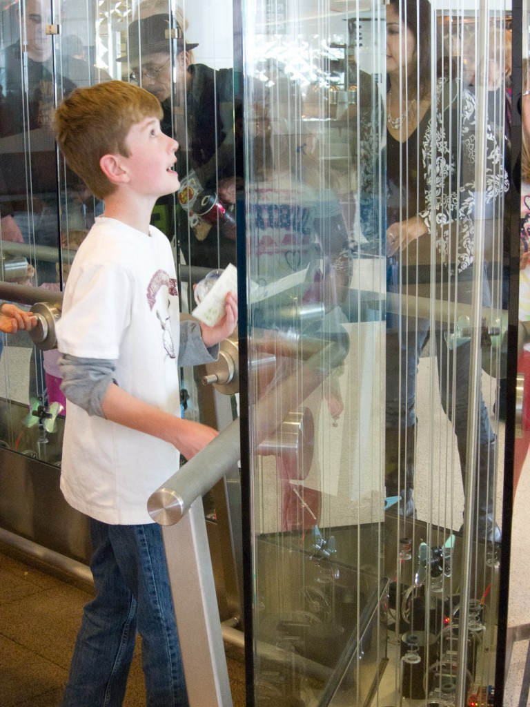"The cranks transport small ""butterflies"" to the top of the glass case, where they drop glittering to the ground."