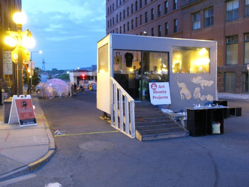 """Art Shanty Projects Disperse"": Board Shanty, Snap Shot Shanty, ParaDICE, and Art Swap Shanty on Broadway St. in Lowertown."